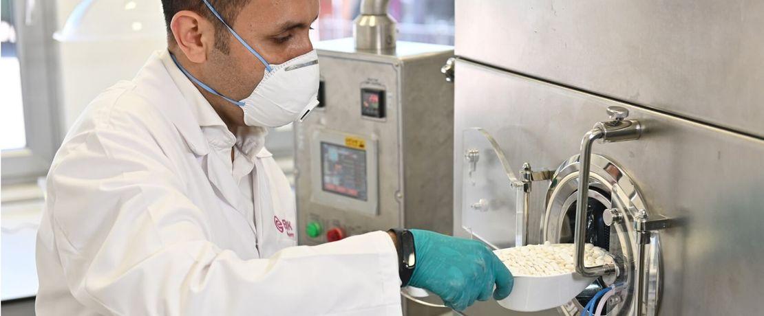 Man adding pills into a coating machine.